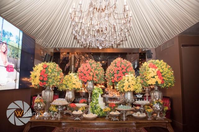 Mesa do bolo com doces, flores e peças douradas. Club A, no World Trade Center em São Paulo.
